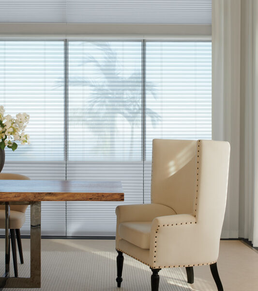 traditional living room with white armchair and large windows with duoilte dual shades silhouette window shades by hunter douglas in Minneapolis