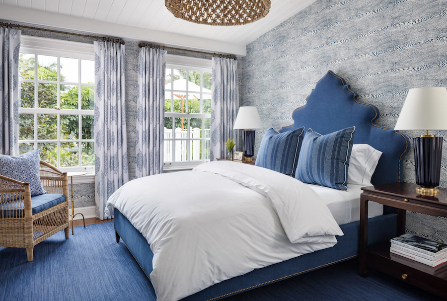 blue upholstered bed in bedroom with wallpaper
