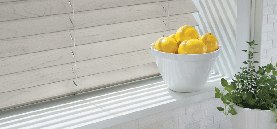 Window sill with faux wood blinds in kitchen.