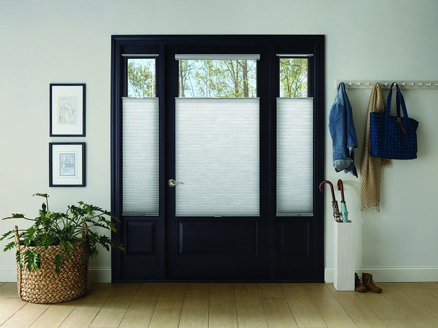 Honeycomb shades adding increased safety on entryway door.