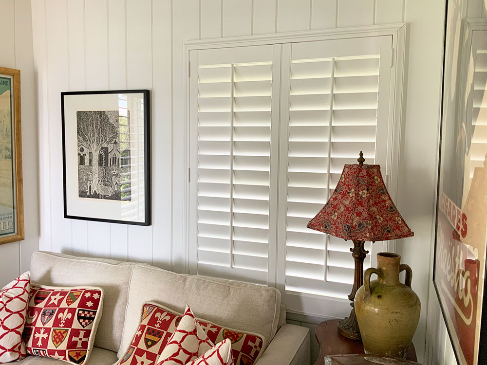 living room featuring heritance hardwood shutters hunter douglas st. paul aero drapery and blinds