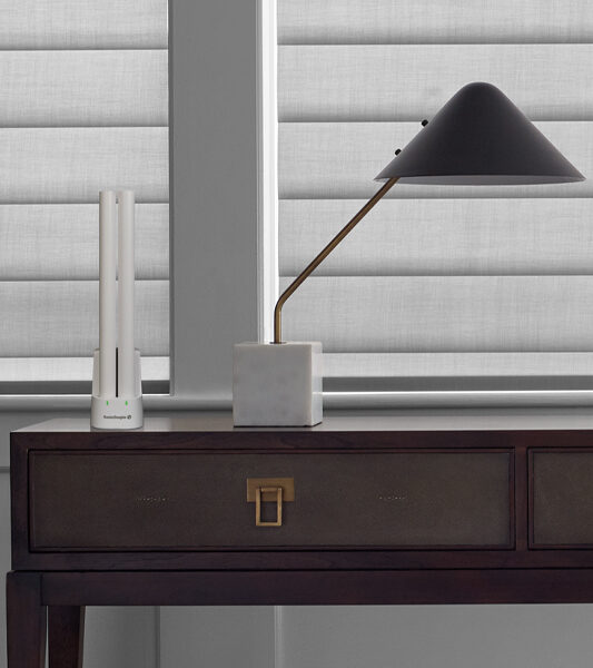 desk and lamp with powerview remote next to closed window blinds