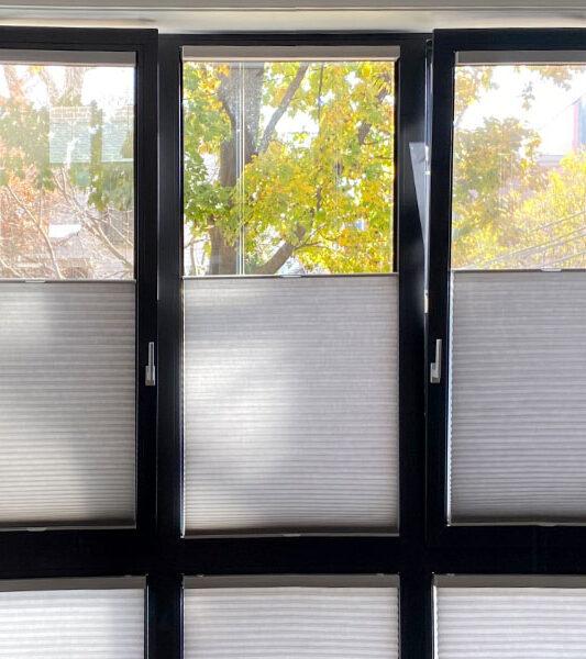 black window frames with gray honeycomb shades on European tilt turn windows in Burnsville MN