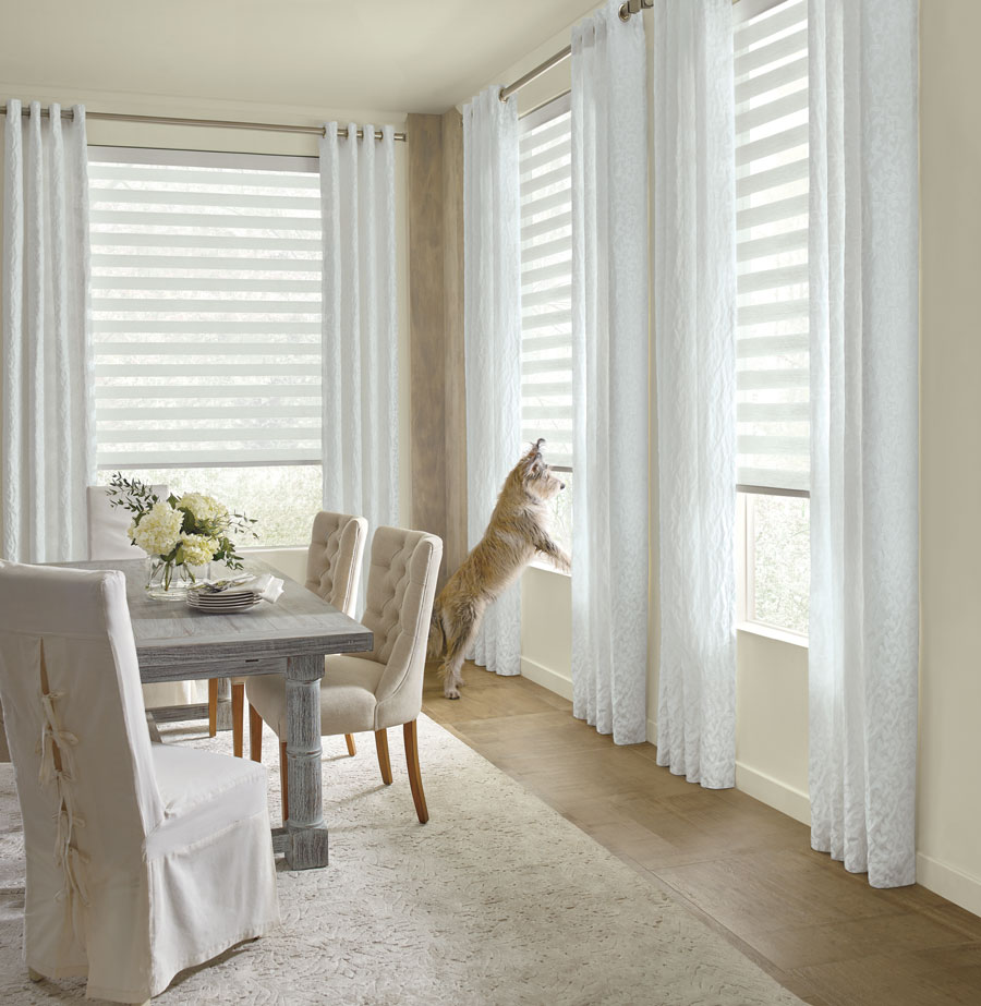 white dining room with white drapery panels and dog on window sill in Burnsville MN